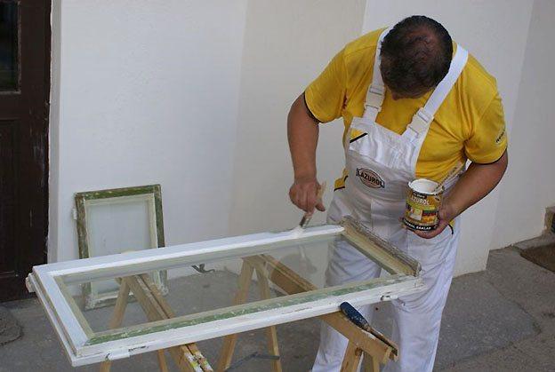 Нанесение краски на отремонтированное старое советское окно